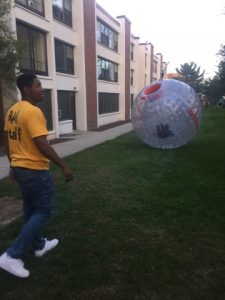 student plays with 5 foot tall inflatable ball at Homecoming block party