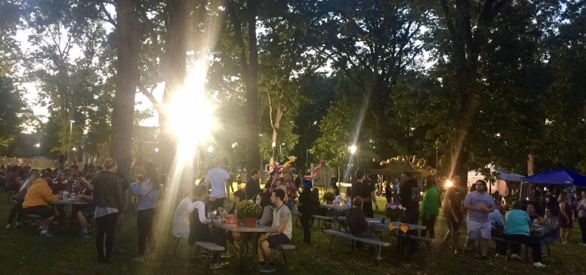 sunlight steams through trees to illuminate students sitting at tables at Homecoming block party