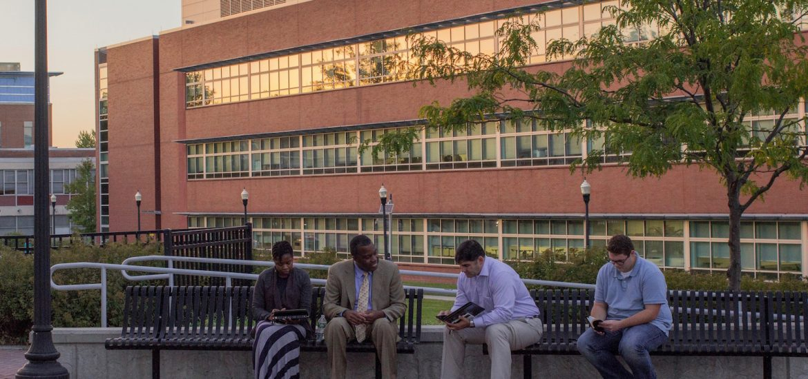 Four people sit on a bench in front of Science Hall at sunset.