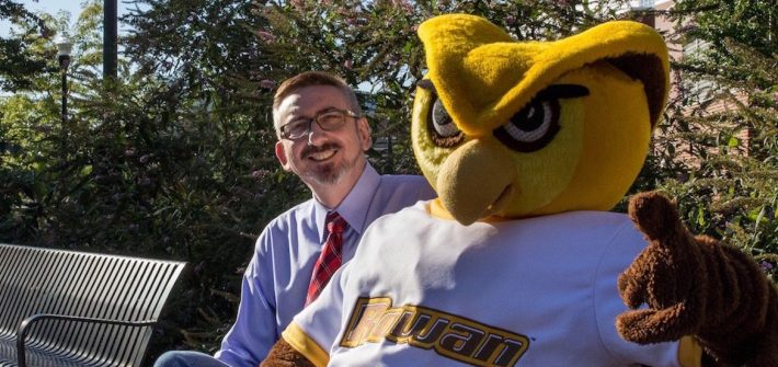 Senior Vice President Jeff Hand sits on a bench with the Rowan mascot giving a thumbs up