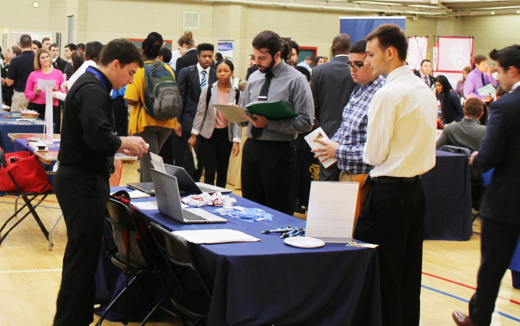 students walk through a career fair, past employer tables