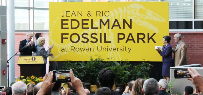 yellow sign unveiled for the Jean & Ric Edelman Fossil Park, as people clap