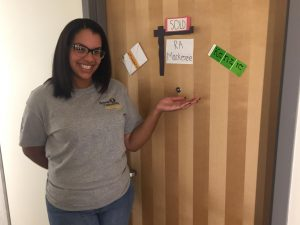 Resident Assistant Mackenzie Brown stands next to her residence hall door adorned with her name.