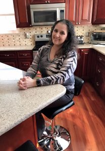 Mom Monica sits at a kitchen table with her hands folded.