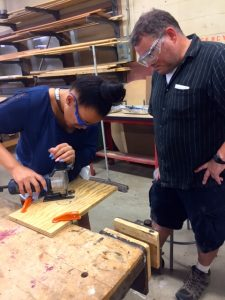 Student working on building project with wood