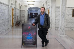 director stands in front of Dracula sign