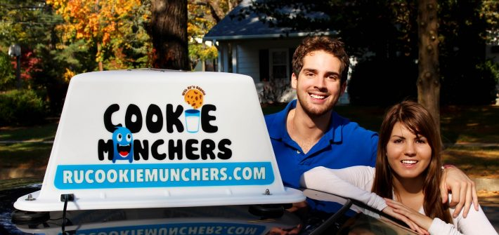 "Cassie Aran and Brandon Lucante pose with their new car sign for ""Cookie Munchers"""