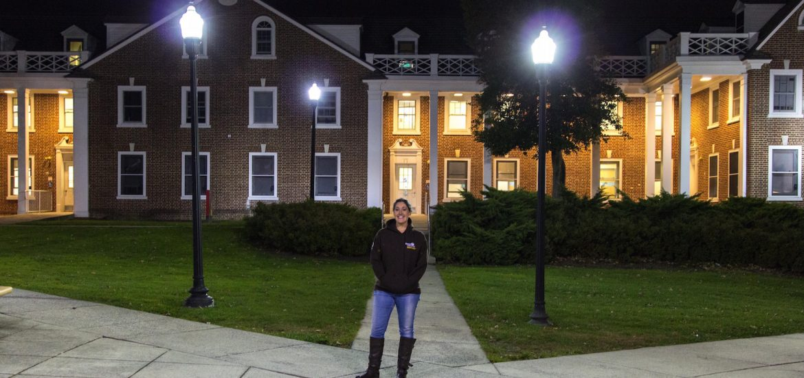 Student stands in front of dorms