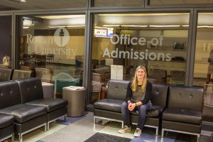 admissions ambassador Haley Schappell sits outside of the Office of Undergraduate Admissions
