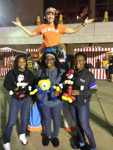 Rowan grad on stilts poses with students and balloon animals