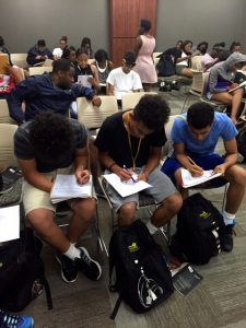 CHAMP Program students completing some work writing in notebooks