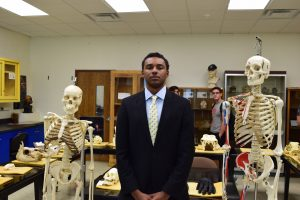 student stands with skeleton