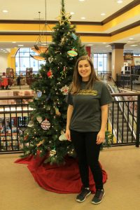 Elyse Baroncinni posing next to the Christmas Tree in Barnes and Noble
