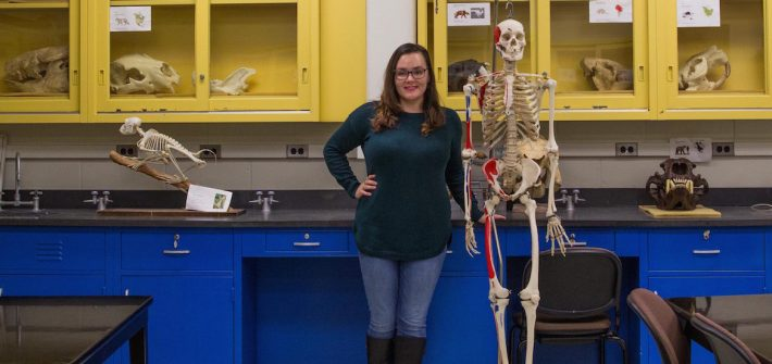 student sits in museum lab next to skeleton