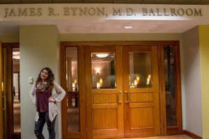 student poses in front of ballroom