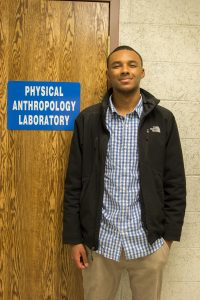 student stands with lab