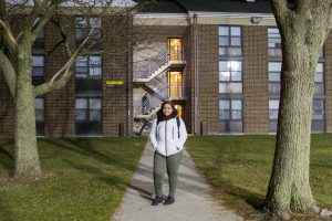 student stands in front of Edgewood Apartments