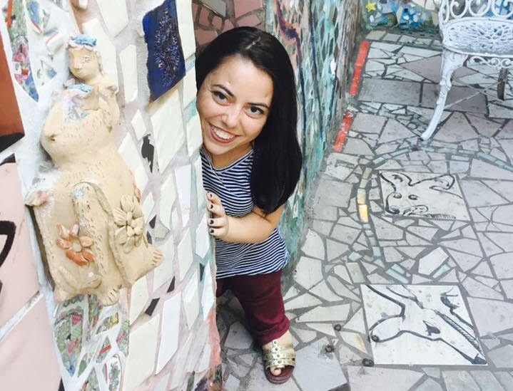 Mackenzie Trush smiles from behind a wall filled with mosaic art