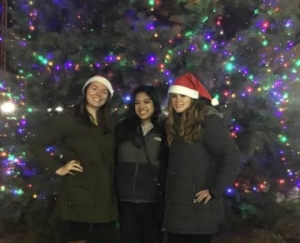 3 friends stand in front of the Glassboro Christmas tree