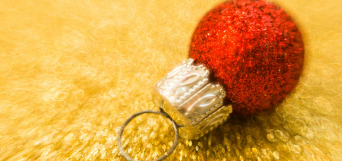 red Christmas ball against a gold background