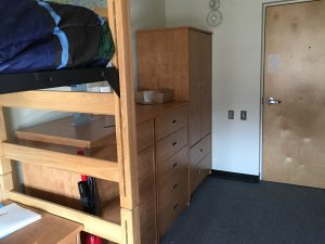 view of armoire and dresser set up in dorm
