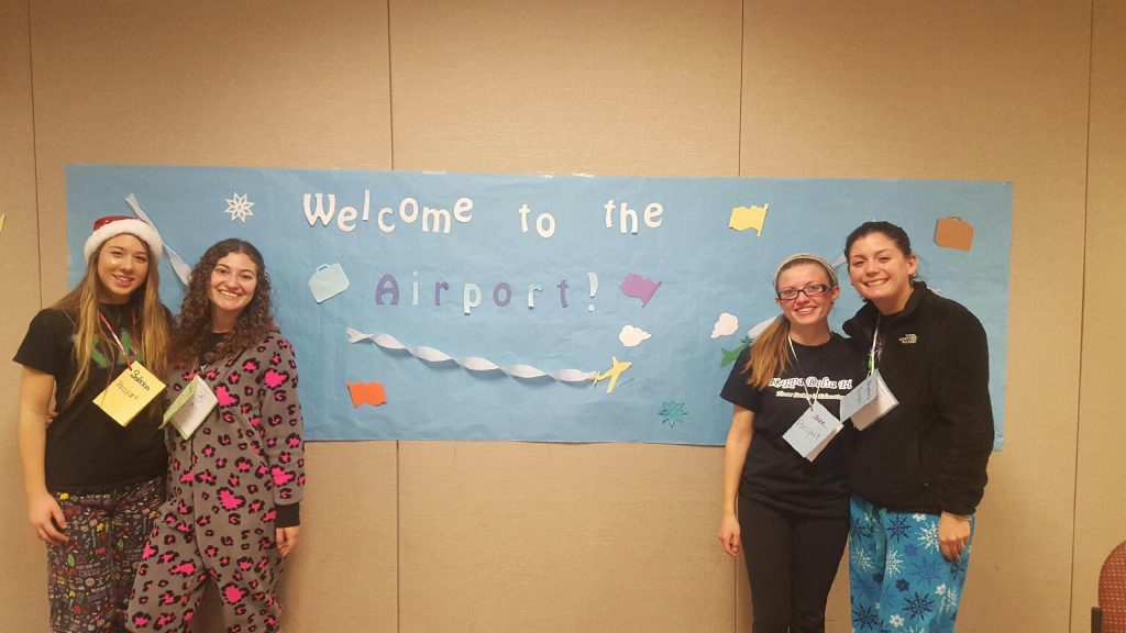education students in pajamas stand near a banner for their make believe airport
