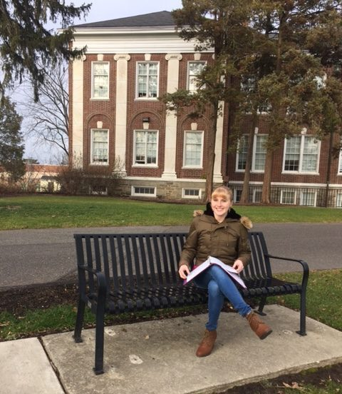 student studies on a bench outside of Bunce Hall