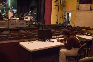 student writes in theatre, with empty theatre in front of him