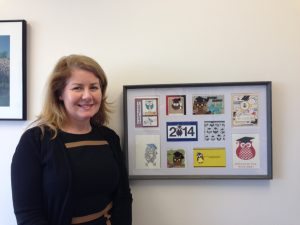 Associate Vice President Rory McElwee, Ph.D. stands near owl art in her office in the Advising Center.