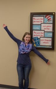 student in front of Dr Seuss reading sign, arms outstretched
