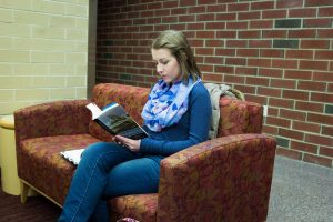student studies in lounge, reading a book sitting on a couch