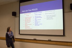 student gives presentation, turned toward screen