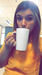 student sips coffee while studying at her internship