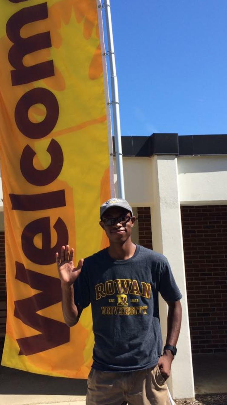 Rowan Choice student Davon waves while standing in front of a welcome banner