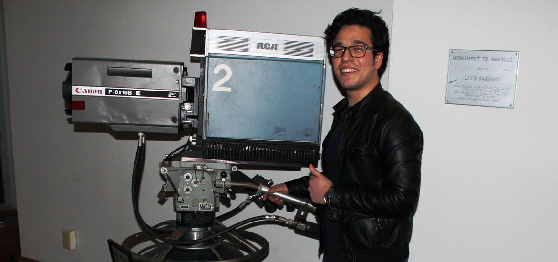 Rowan RTF Student Frank Villarreal poses next to the antique canon camera