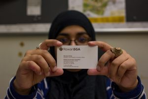 student holding SGA business card