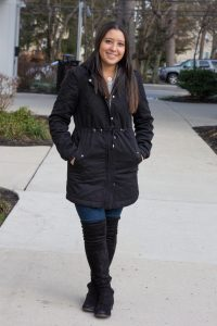 student portrait Carly Sanchez stands outside, wearing a black winter coat with hands in her pockets