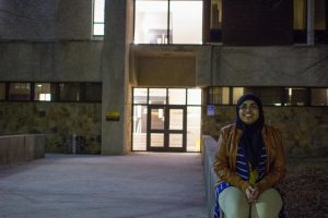 student sits outside Robinson Hall