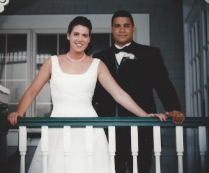 Julie and Bernard on their wedding day, in a white dress and a tux, behind a porch railing