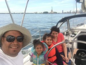 Bernard, Julie and their two daughters pose on a sailboat on the Hudson River