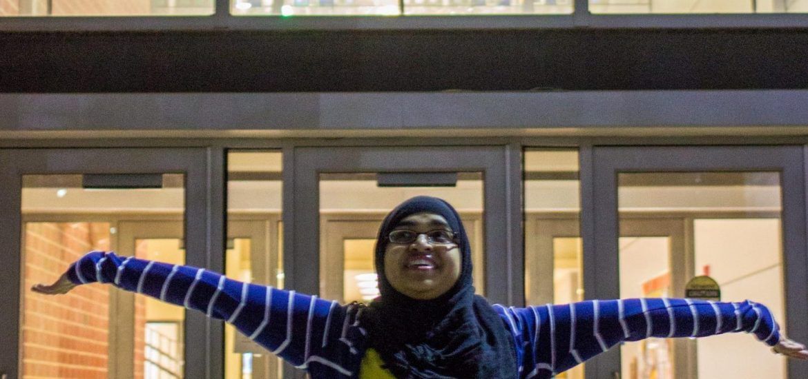 Naveen stands arms outstretched in front of stained glass at James Hall