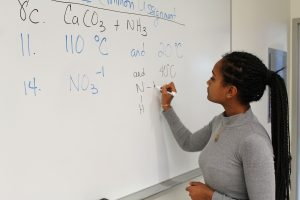 Tsion Abay Rowan Student writes a chemical formula on the board