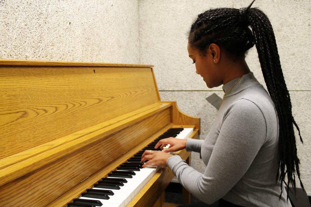 Tsion Abay practice playing the piano at Rowan Wilson Hall