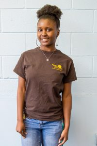 student Troi Foster stands in Mimosa Hall, wearing a brown Rowan shirt