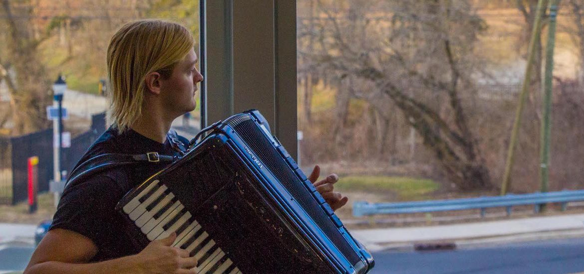 Steve looks out the window at the Glassboro water tower while playing accordian