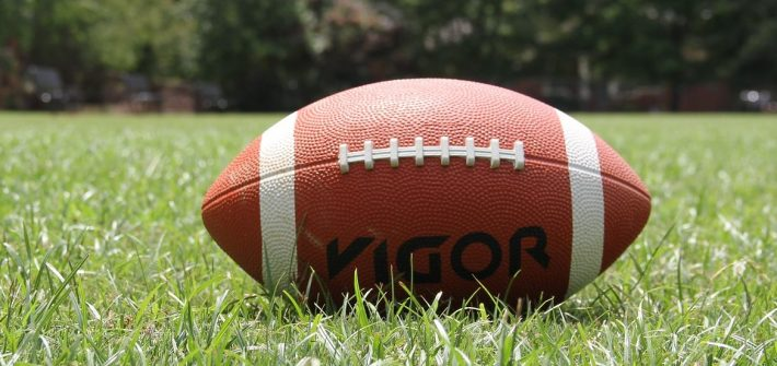 a brown football on green grass