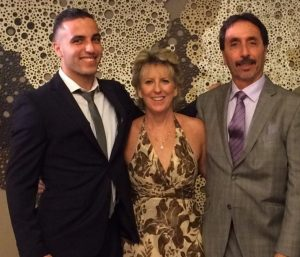 Blog author wears a suit and tie posing with his parents, dressed in formal wear.