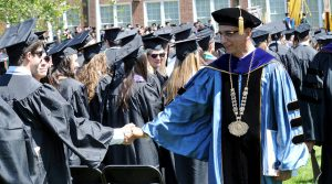 President Houshmand shakes hands with a Rowan graduate at commencement.