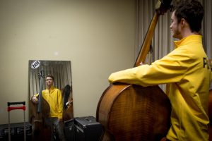 student stands in bass room, with reflection of his instrument in front of him in the mirror