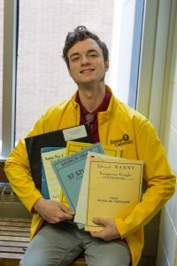 student holds stacks of music comp books